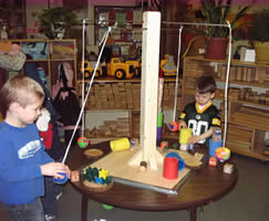 boys playing with a pendulum in the block area